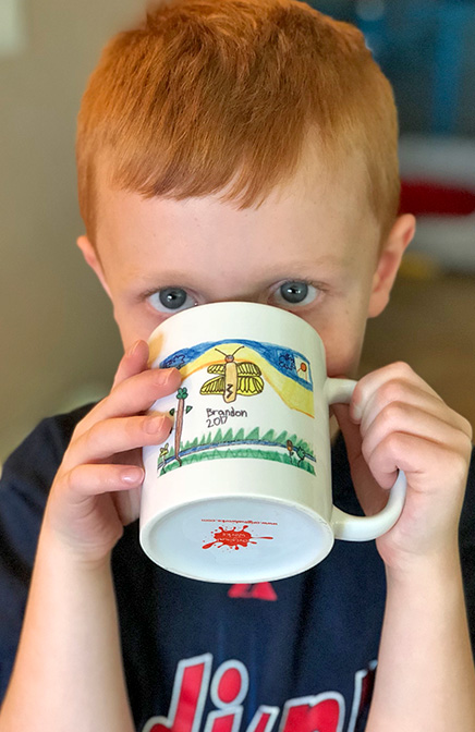 child drinking out of his artwork mug