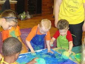 Campers and counselors being creative and having fun working on their group murals.